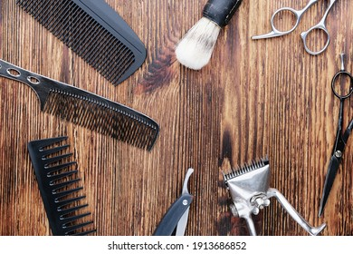On a weathered wooden surface are old barber tools. Vintage manual hair clipper, combs, razor, hairdressing scissors. top view, flat lay. Barbershop background. horizontal orientation.