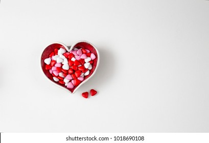 on a white background candy in the form of a heart in a heart-shaped vase