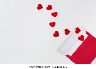 on a white background an envelope and red satin hearts are flying from it