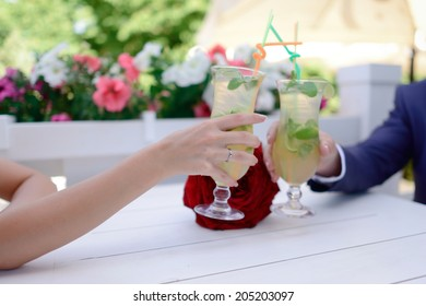 on white background hands of bride and groom with wedding ring holding glasses mojito