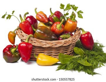 on white background harvest vegetables colorful peppers in basket and salad greens