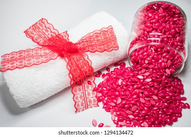 on a white background is a red granular wax in a glass jar and a white towel with a red bow.
