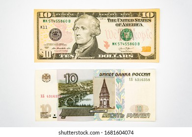 On a white background are two paper bills of 10 US dollars and another 10 Russian rubles