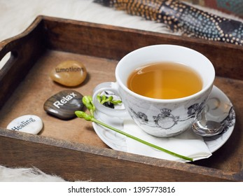 On a white flokati carpet a didgeridoo and a wooden tablet with a filled teacup on it. Decorated with a flower and three labeled pebbles, Healing, Relax, Emotions. View 1