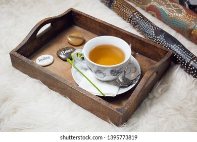 On a white flokati carpet a didgeridoo and a wooden tablet with a filled teacup on it. Decorated with a flower and three labeled pebbles, Healing, Relax, Emotions. View 2
