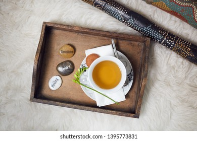On a white flokati carpet a didgeridoo and a wooden tablet with a filled teacup on it. Decorated with a flower and three labeled pebbles, Healing, Relax, Emotions. Top view
