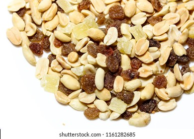 On a white isolated background lies a mixture of nuts and fruits. The mixture consists of peanuts, candied fruits, raisins and dried bananas.