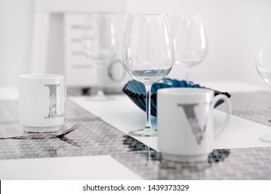 On a white kitchen dining table on place mat tea cups close up focus on empty transparent clear wine glass at the cozy modern room