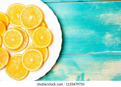 on a white large round plate is sliced orange, blue background and oranges
