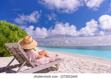 On white sand tropical beach, young adult woman lying on a sun bed.
