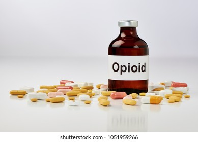 On a white surface stands an ampoule on which opioid is written. There are many tablets around the ampoule. The background is white