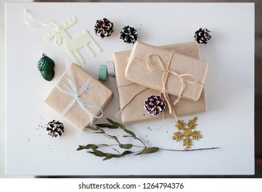 on the white table laid out gifts in boxes, tied with ribbons, Christmas toys and decorations