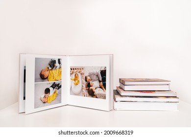 on white table open photobook from photo shoot of family with newborn baby. preservation of important moments of life in photo album. result of work of photographer and designer. polygraphy.