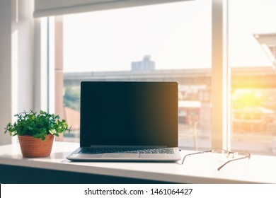 On a white table, there is a notebook computer used for business communication. And having glasses, plant pots placed near each other, by the window with shining light in the home office