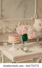 On white table vases with lilac and hydrangea, cake and picture in frame