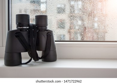 On a white windowsill by the window with raindrops on the glass is a black binoculars for observing neighbors. Fascinating observation of the environment from the window of the house