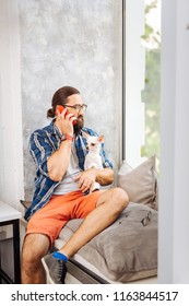 On window sill. Dark-haired handsome freelancer sitting on window sill speaking on the phone holding dog