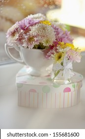 on the windowsill in a wet glass is white vase with a bouquet of flowers
