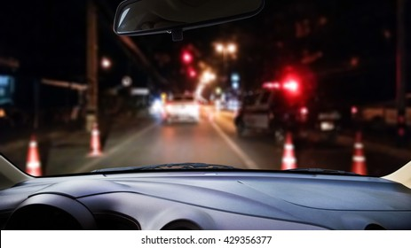 On the windshield,  blur image of police checkpoint at dark night as background.