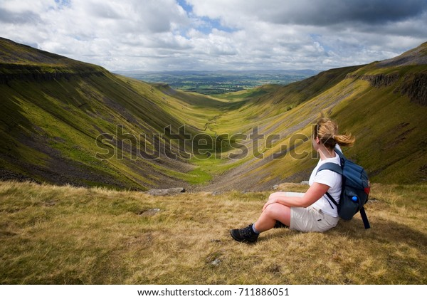 On a windy day a walker sits enjoying the view from a Cumbrian beauty spot called High Cup Nick in England, UK.