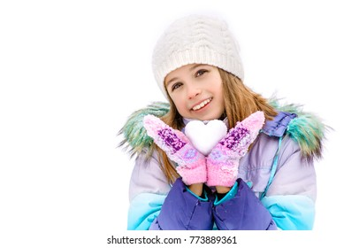 On a winter day girl holding a snowball in the shape of a heart. Girl standing on a white snow jacket, hat and mittens. Girl gives heart of the snow. Isolated on white background