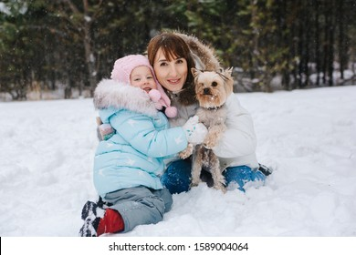 On a winter day, a woman and a girl are sitting in the snow against the background of a forest, hugging and holding a Yorkshire Terrier dog in their arms and looking at the camera.