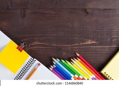 On a wooden background, colorful pencils and notepads.