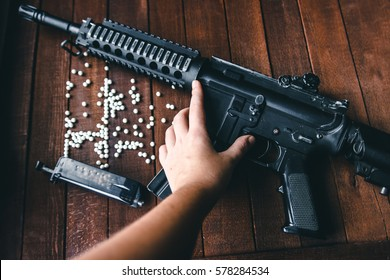 on wooden background hand pointing to the foregrip airsoft rifles, weapons