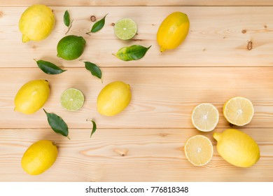 on a wooden background, lie different lemons in order along with green lime
