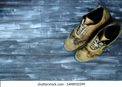 On a wooden background a pair of brown shoes. One pair of leather sneakers is very worn. Black Friday - time to buy new sneakers. Sneakers in the upper right corner are laced with laces. Close-up