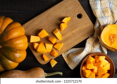 On a wooden black table lie pumpkins of various sizes and shapes, a dishcloth and a bowl of sliced pumpkin. In the center of the frame is a cutting board with sliced pumpkin. Top view.