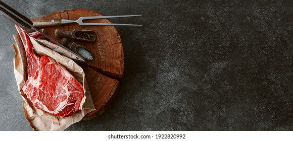 on a wooden block for meat a fresh raw tamahawk steak or a cowboy steak with a butcher's chopping ax for meat, next to it is a mixture of peppers and coarse salt, milled with thyme. fresh beef steak