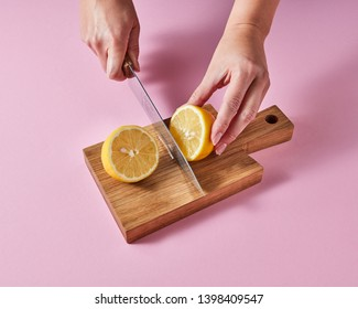 On a wooden board the hands of a woman cut a ripe lemon for making a vitamin drink around a pink background with space for text.