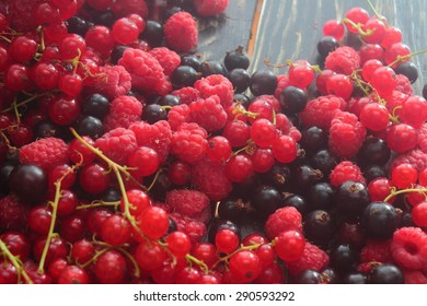 on a wooden board lots of fruits raspberries, currants