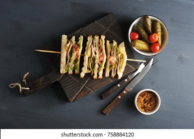 On a wooden board a sandwich of white bread. The filling of the sandwich consists of bacon, cheese and ham.  Next to cutlery, mustard and pickles. Dark wooden background. View from above. Close-up.