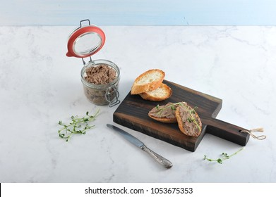 On a wooden board slices of fried baguette with liver pate. Next to the pot with pate, young greens of peas, a knife. Light background. Close-up.
