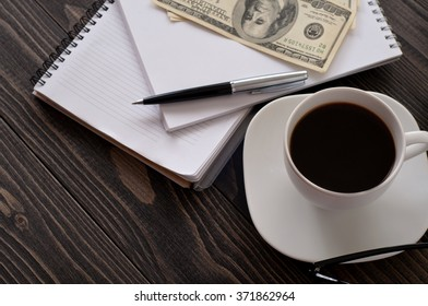 On wooden office desk closeup, stack notepads, pen, cup of coffee and money. top view with copy space