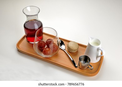 On the wooden plate stood a glass jug with red tea and a glass of red fruit, an iron spoon of milk biscuits, and a sumptuous breakfast.