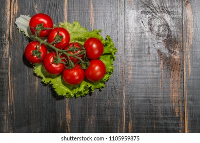 on wooden table background branch red tomatoes on a fresh salad plate