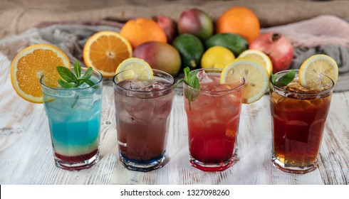 On a wooden table; Blue Hawaiian, Ice Tea, Strawberry Mojito and Forest Fruity Iced Drink.