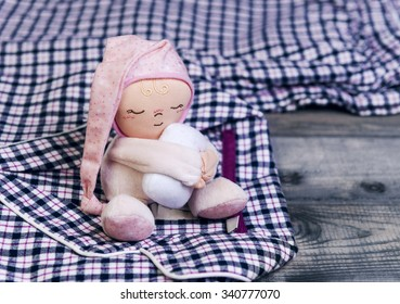 On a wooden table checkered flannel pajamas and a sleeping soft toy man in a pink cap with a pillow in his hands
