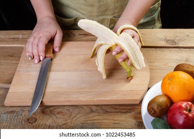 On a wooden table on a cutting board, a woman removes the skin from a banana to make a fruit cocktai