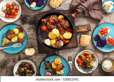 On the wooden table a different food, fried meat with vegetables in a pan, salad and snacks, top view