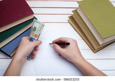 On a wooden table hardcover books and the sheet of paper on which in hands the ink handle and write. - Shutterstock ID 586013255