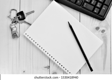On the wooden table are keys to the car with a keychain in the form of a car, a notebook and a pencil next to it. The edge of the keyboard is visible.