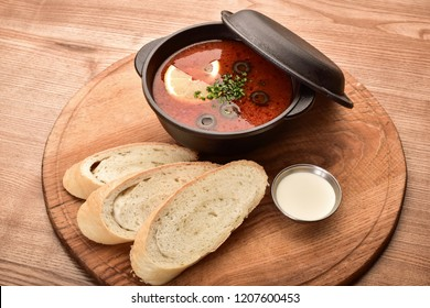on a wooden table pieces of bread and a hodgepodge in a black saucepan