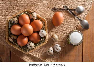 On wooden table sackcloth. On sackcloth three mottled quail eggs and one chicken egg, two tea spoon, salt in salt shaker and wicker basket. Many different eggs on straw in basket.