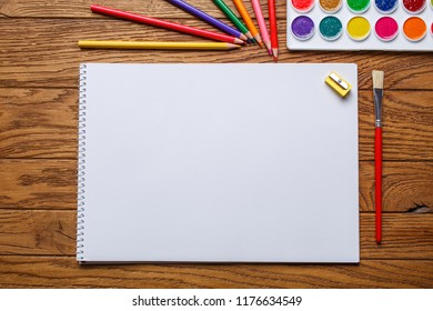 On the wooden table there is an album for painting, paint, pencils and brushe. On a wooden background. Top view, flat lay. copyspace