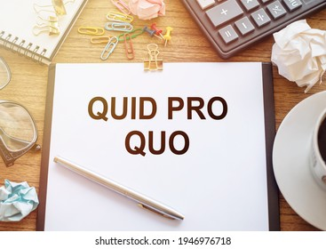 On a wooden table there is an office sheet of paper with the text Quid Pro Quo. Business workspace with calculator, glasses, pen, crumpled paper and cup of coffee.