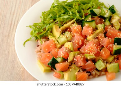On wooden table traditional hawaiian raw salmon poke bowl with avocado, cucumber, tomato, sesame seeds, lettuce and rice in bottom. Top view.